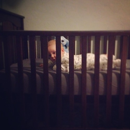 Watching his big brother from his crib.