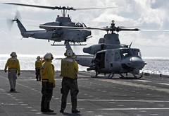 Aviation Boatswain's Mates (Handling) direct an AH-1W Cobra helicopter, left, assigned to the Flying Tigers of Marine Medium Helicopter Squadron (HMM) 262  and an MH-60S Sea Hawk helicopter assigned to Helicopter Sea Combat Squadron (HSC) 25 during takeoff Sept. 13 from the flight deck aboard the forward-deployed amphibious assault ship USS Bonhomme Richard (LHD 6) during a certification exercise. (U.S. Navy photo by Mass Communication Specialist 2nd Class Michael Russell)