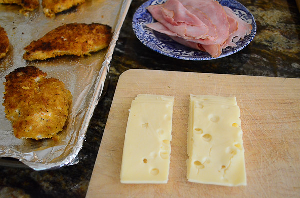 A plate of ham and slices of cheese ready to be placed on the chicken.