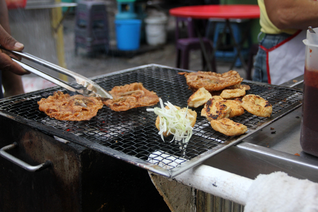 Roasting the rojak ingredients over charcoal