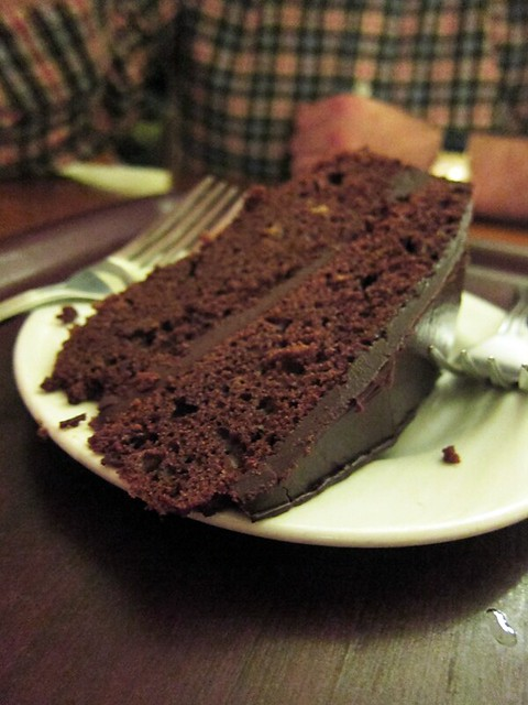 Big slice of double-layer chocolate cake on a plate, with a thick chocolate frosting between the layers and on top.