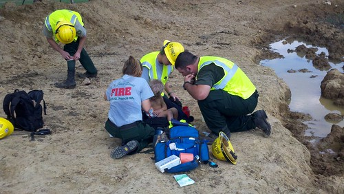 Rescue crews from the Ozark-St. Francis National Forest attend to three-year-old Landen Trammel whom they found Wednesday, Sept., 12 in Stone County, Ark. From left are Jamie Martin, Carol Swboni and Bradley Taylor who spotted the toddler playing in a mud puddle.  Photo credit: Courtesy of Fox16.com