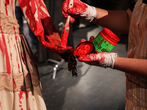 Costumer applying fresh blood paint color to dress