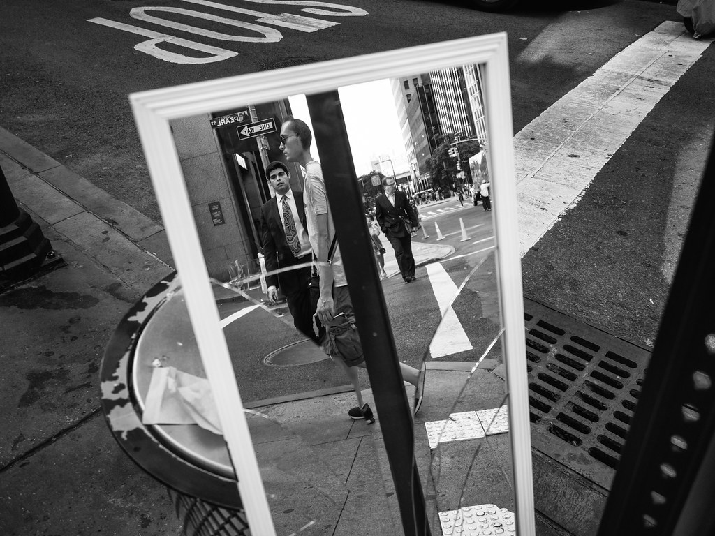 black and white image of a broken mirror on a wall street intersection in new york