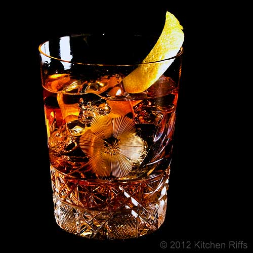 Old-Fashioned Cocktail in Crystal Rocks Glass with Lemon Twist Garnish, Black Background