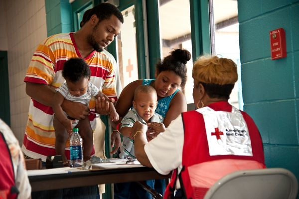 red cross volunteer helps child
