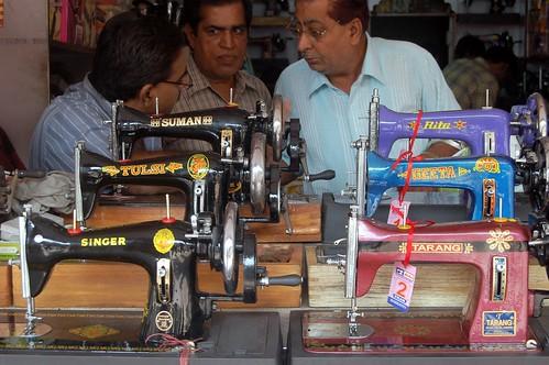 Drei Händler beraten hinter einer Front von Nähmaschinen