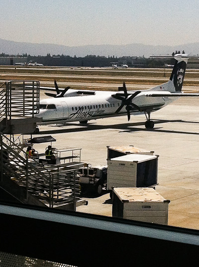 A twin propeller airplane parked at the airport.