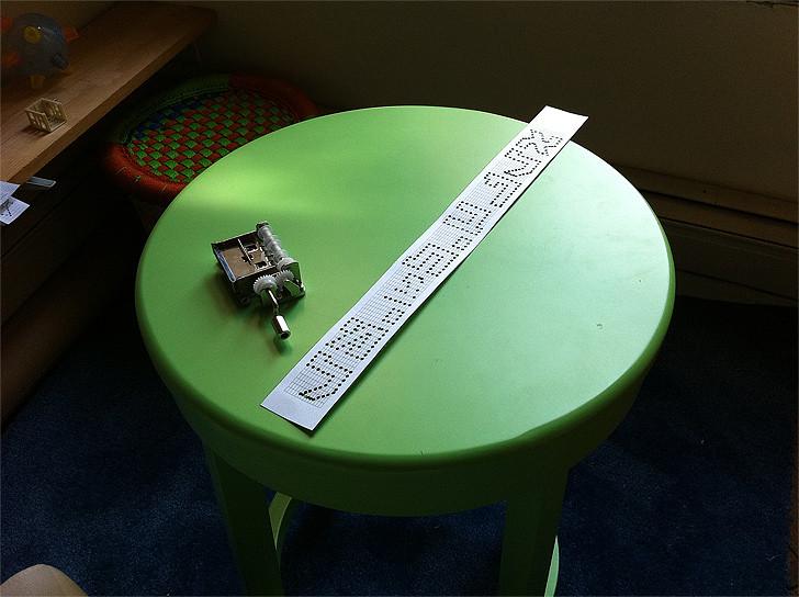תיבת הנגינה לצד נייר מנוקב בצורות אותיות