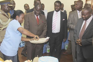 President Mugabe watches as Harare Polytechnic student Elizabeth Rubaya cuts a cake made from the masau fruit (Ziziphus Mauritiana) for him at the Research and Intellectual Exposition at the University of Zimbabwe September 6, 2012. by Pan-African News Wire File Photos