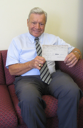 Peter Vallone holding the report card of his mother, Leah Palmigiano.