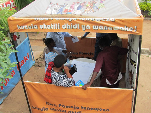 "Group work under an awning that says ""Prevent violence against women"""