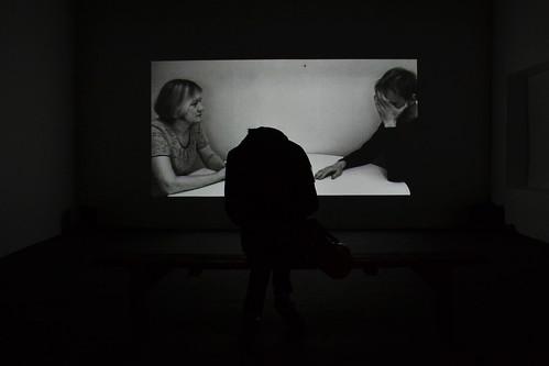 tres personas en una sala de cine, una persona escucha, un hombre setoma la cara, una mujer agacha la cabeza