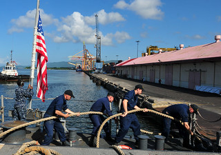 Sailors heave in a mooring line.