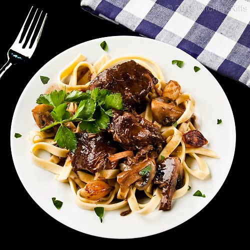 Boeuf Bourguignon on Plate with Homemade Noodles and Parsley Garnish