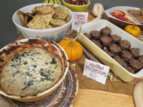 Closer view of a bowl full of spinach-artichoke dip and a platter of stuffed mushrooms.
