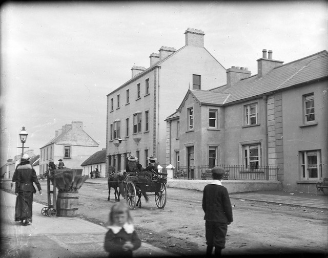 Street in a village, with horse and cart, and bystanders = Main Street, Bundoran