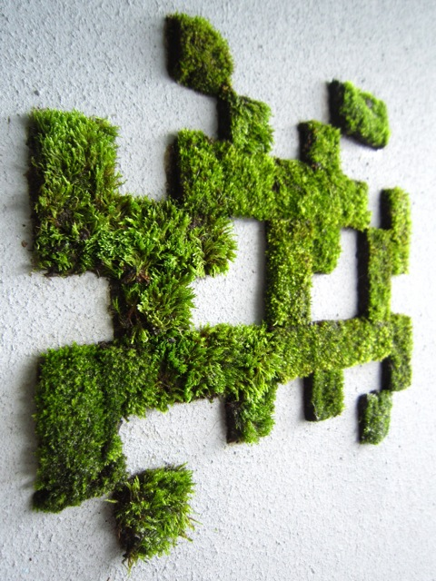 moss graffiti in the geometric shape of Space Invaders