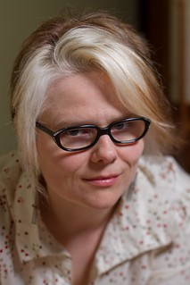 A headshot of Sara Ryan, a white woman with thick black framed glasses, a polkadot collared shirt, and blond hair.