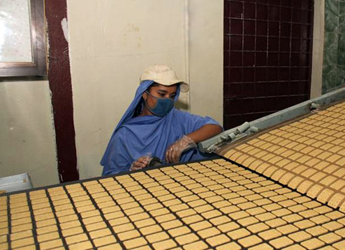 A Bangladeshi factory worker monitors the production of biscuits made from U.S. donated wheat. The donation was delivered to the World Food Programme, a Foreign Agricultural Service (FAS) McGovern-Dole program participant that works to provide food assistance in more than 73 countries. The biscuits will be distributed to about 2,000 schools in the poorest areas of Bangladesh.  (Photo courtesy U.S. Embassy New Dehli)