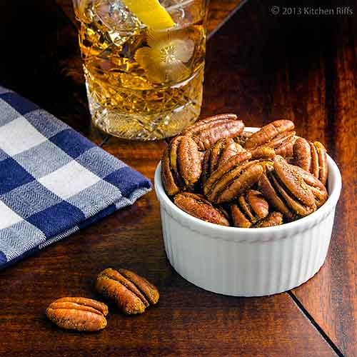 Spiced Roasted Pecans in Ramekin with Cocktail in Background