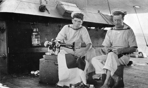 Two signalmen of HMAS Melbourne mend their clothing at sea by Australian War Memorial collection
