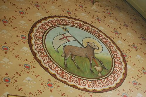Das Wappen zeigt ein Lamm, dass mit Herzblut einen Kelch füllt.