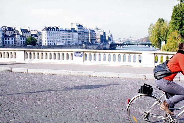 red cyclist on seine bridge paris