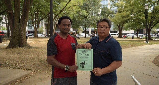 Albert Townsend (left) and Unchu Na (right) hold a flyer for Weldon Moore's memorial. | Photo by Jerome Dineen