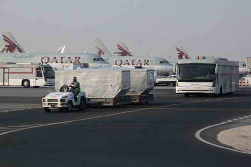 Cargo containers and transfer buses pass Qatar Airways jets at Doha