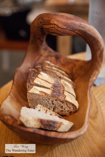 Artisan wooden bread basket filled with slices of country bread