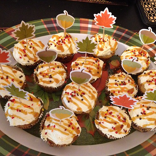 Apple spice cupcakes with apple pie filling in the middles and buttercream frosting with a caramel drizzle and autumn leaves sprinkles