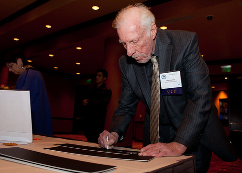 Dean Jensen, a Hall of Fame honoree, signing a plaque at the Hall of Fame dinner on Fri., Oct. 26, 2012.