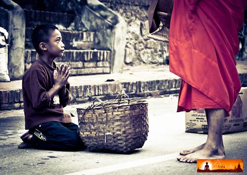 Niño pidiendo comida a un monje en las calles de Luang Prabang