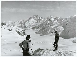 Two Japanese skiers (Yuichiro Miura on right) survey the ski-run down the Tasman Glacier from the glacier's head. Mt. Cook.