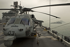 An MH-60S Sea Hawk helicopter sits on the flight deck of amphibious assault ship USS Bonhomme Richard (LHD 6) as amphibious dock landing ship USS Tortuga (LSD 46), right, arrives in Hong Kong Oct. 30 for a port visit. (U.S. Navy photo by Mass Communication Specialist 1st Class Michael Russell)