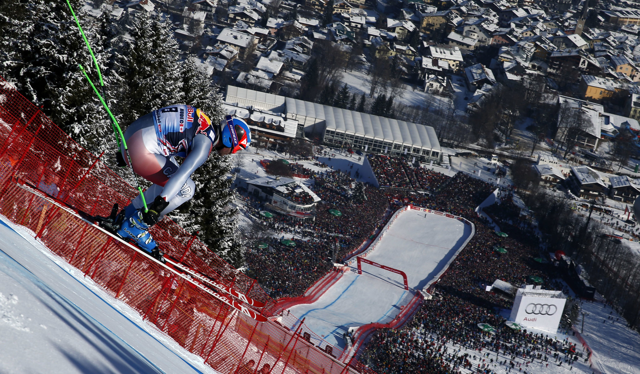 Jan Hudec catches air, with the finish area of the Kitzbühel downhill visible in the background.