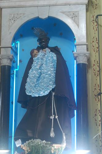 Eine Figur mit Häuptlingsschmuck hält ein Blütenbekränztes Jesuskind