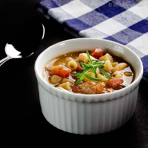 Pasta e Fagioli in white ramekin with napkin and spoon