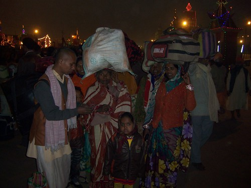 Groups of women with heavy luggage on their head, arriving at the Kumbh Mela