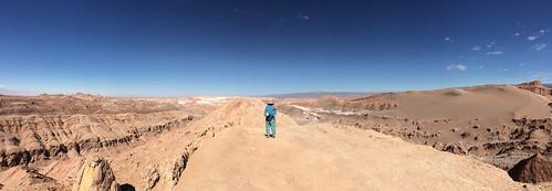 Le désert d'Atacama: Miss V au sommet d'une crête (Valle de la Luna). Vue sur un petit salar au loin.