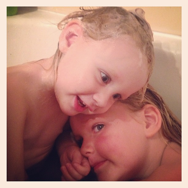 Loving up each other in their purple bath! #bathtime #sisters