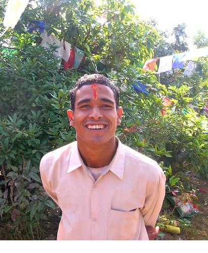 Happy Shivite, religious Nepalese man, Tibetan prayer flags, Nepal - photo by Glenn by Wonderlane