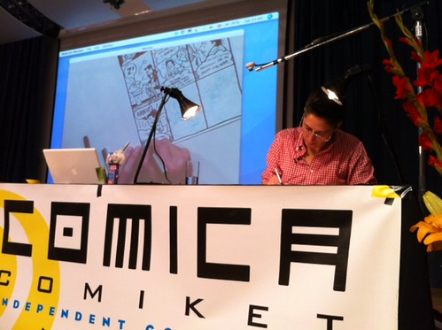 comiket drawing with screen in background