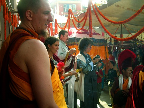 Students, monks, lay people with cameras and offerings, White Umbrella, marigolds, Sakya Lama procession, Tharlam Monastery Courtyard, Boudha, Kathmandu, Nepal, photo by Steve D. by Wonderlane