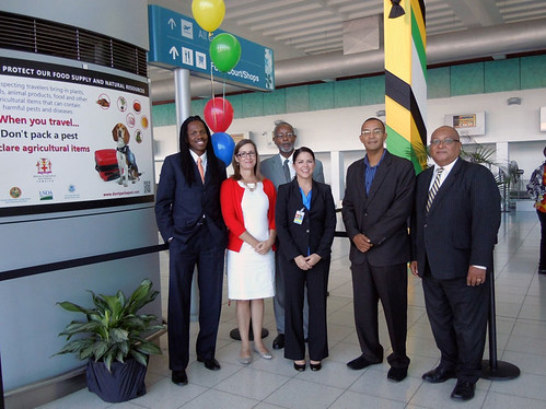 "Launch of ""Traveler's Don't Pack a Pest"" outreach campaign at Norman Manley International Airport, Kingston, Jamaica.  From left: Damion Crawford, Minister of State, Jamaica Ministry of Tourism; Shannon Shepp, Deputy Commissioner, Florida Department of Agriculture and Consumer Services; Dr. Raymond Brown, Deputy Chief of Mission, Embassy of United States, Kingston, Jamaica; Jennifer Lemly, Director, Greater Caribbean Safeguarding Initiative, USDA/APHIS; Dr. Marc Panton, Chief Technical Director, Jamaica Ministry of Agriculture and Fisheries; and Major Richard Reese, Commissioner of Customs, Jamaica Customs."
