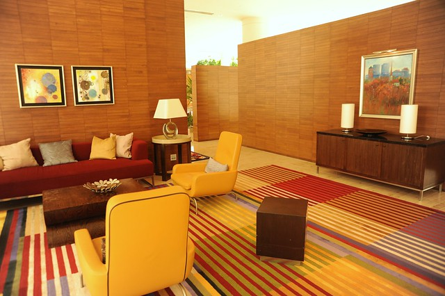 Lounge room, sofas, pillows, armchairs, end tables, lamps, art, sideboard, wood walls, striped carpet, red and yellow, contemporary furniture, Renaisance Hotel, Schaumburg, Illinois, USA