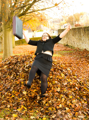 A person in a business suit with a leather briefcase jumping into leaf pile