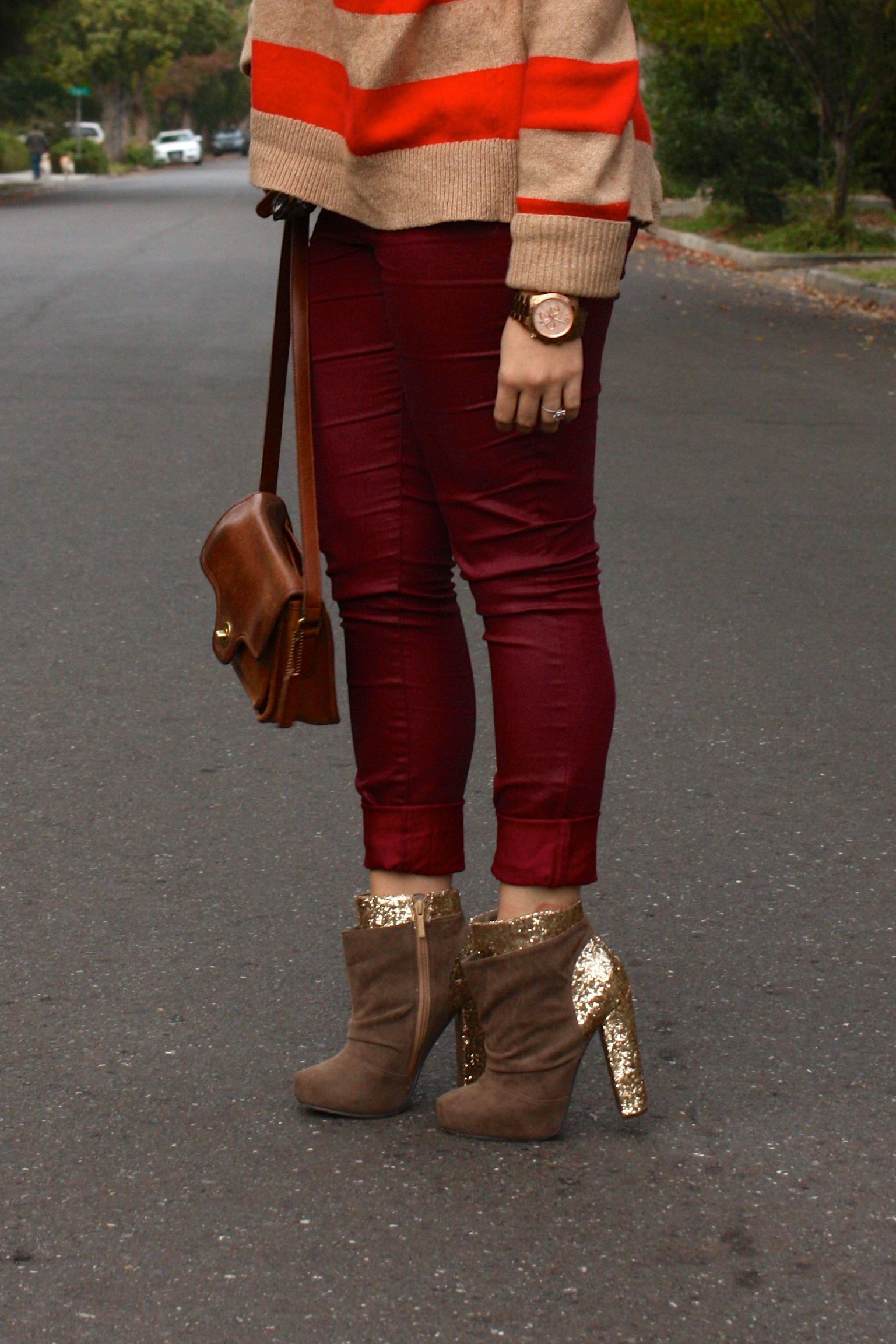 burgundy waxed jeans with orange striped sweater and brown coach bag plus glitter booties