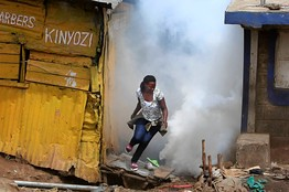 A woman runs to escape teargas in Kenya during clashes with ethnic Somalians. Tensions have escalated since the invasion of Somalia by the Kenyan Defense Forces. by Pan-African News Wire File Photos